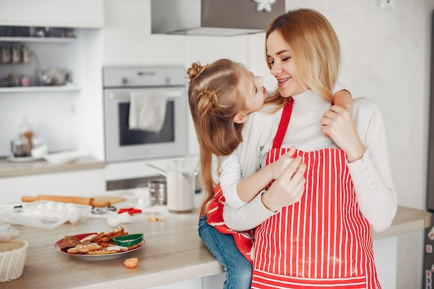 Family sitting in a kitchen with cookies Free Photo