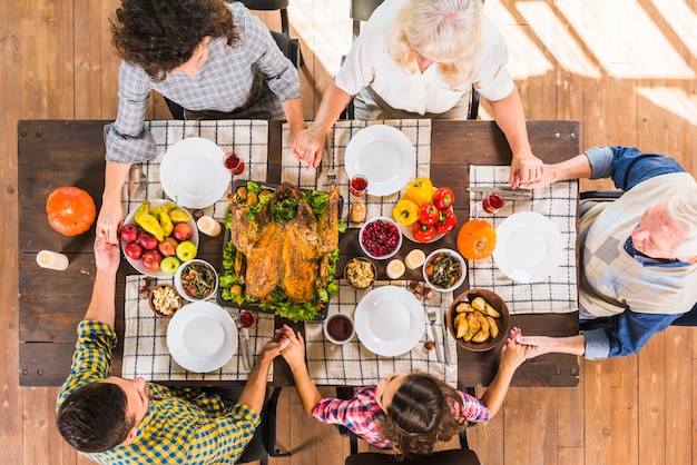 Family sitting at table with holding hands Free Photo