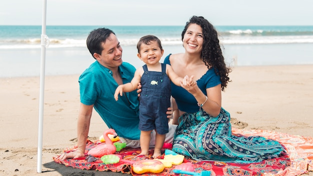 Family sitting together on beach in summertime Free Photo
