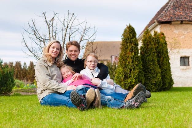 Family sitting together on a meadow in spring Premium Photo