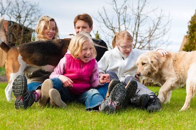 Family sitting with dogs together on a meadow Premium Photo