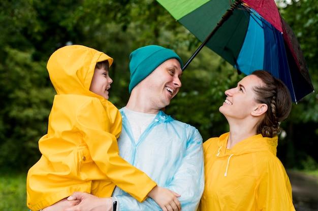 Семья улыбается под зонтиком Бесплатные Фотографии