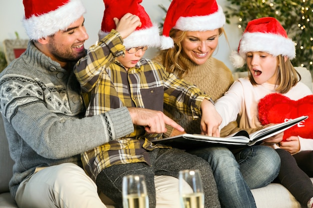 Family smiling with santa claus hats and looking at a photo album Free Photo