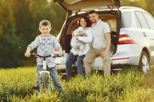 Family in a summer forest by the open trunk Free Photo