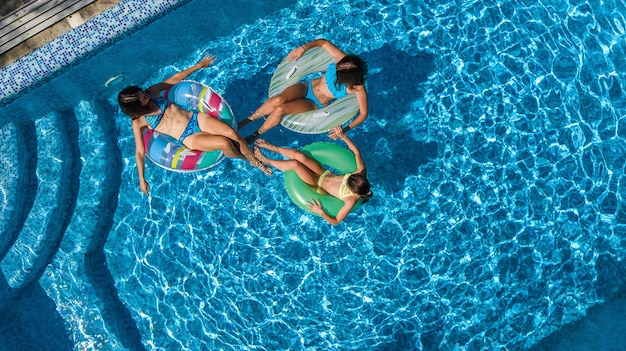 Family in swimming pool from aerial drone view Premium Photo
