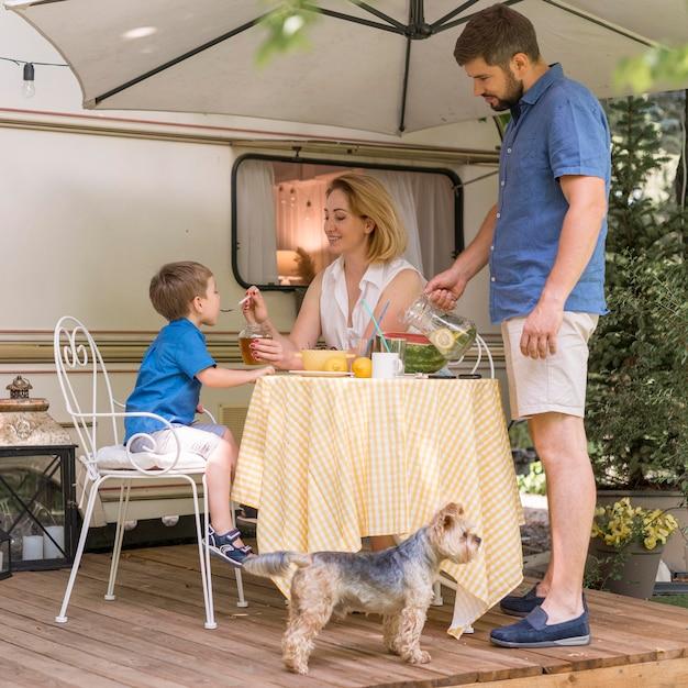 キャラバンの外で昼食を取る家族 無料写真