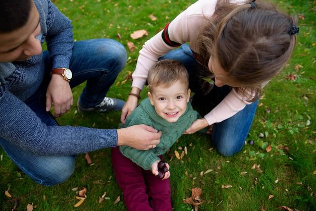 Family of three enjoy autumn park having fun smile Premium Photo