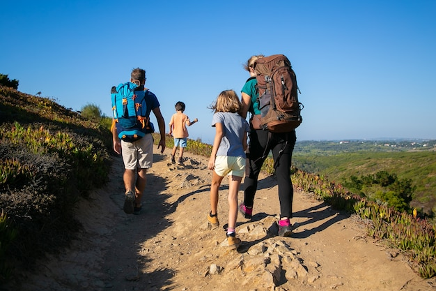Family of travelers with backpacks walking on track. parents and two kids hiking outdoors. back view. active lifestyle or adventure tourism concept Free Photo