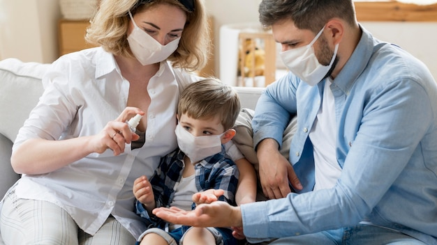 Семья, использующая дезинфицирующее средство и носящая медицинские маски Premium Фотографии