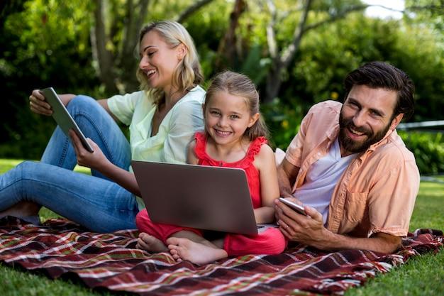 마당에서 편안한 기술을 사용하는 가족 프리미엄 사진