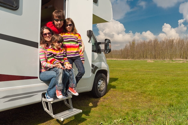 Family vacation, rv travel with kids, happy parents with children on holiday trip in motorhome, camper exterior Premium Photo