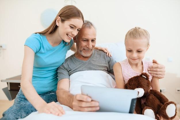 Family visit to elderly man who use tablet Premium Photo