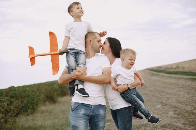 家族がフィールドを散歩し、おもちゃの飛行機で遊んで 無料写真