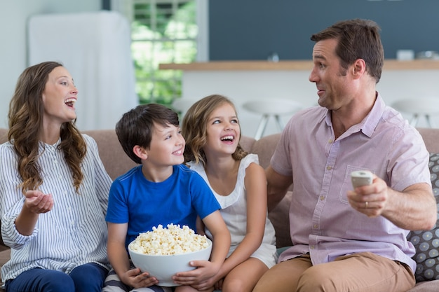 Семья смотрит телевизор и ест попкорн в гостиной дома Premium Фотографии