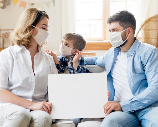 Family wearing medical masks indoors copy space Free Photo