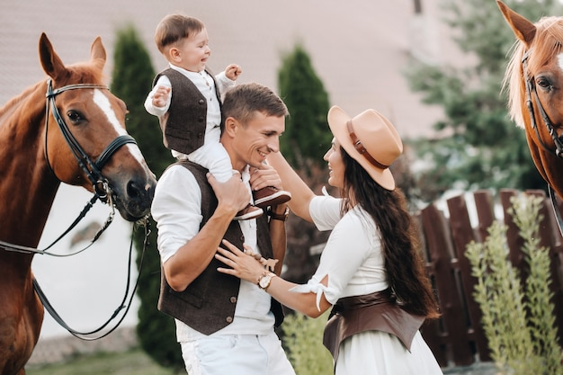 A family in white clothes with their son stand near two beautiful horses in nature. a stylish couple with a child are photographed with horses. Premium Photo
