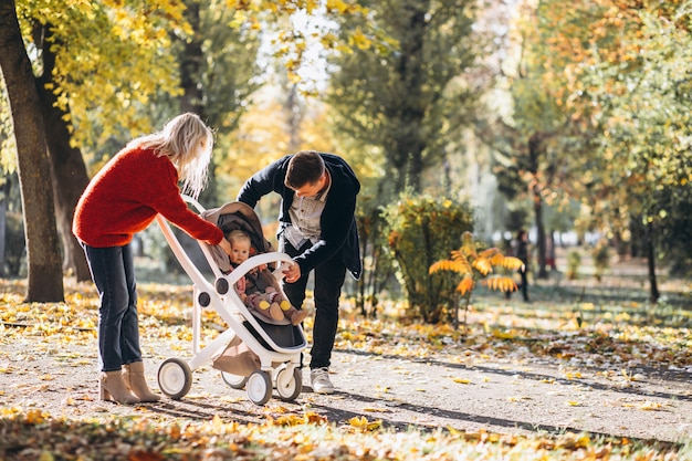 Family with baby daugher in a baby carriage walking an autumn park Free Photo