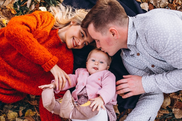 Family with baby daugher lying on leaves in park Free Photo