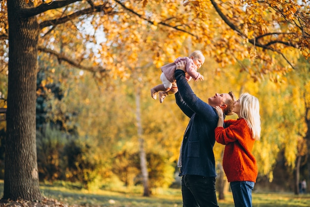 Family with baby daughter walking in an autumn park Free Photo