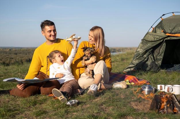 Семья с ребенком и собакой, проводящей время вместе Premium Фотографии