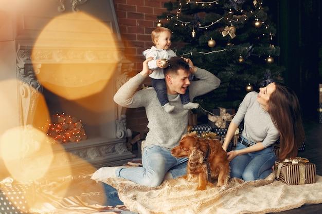크리스마스 트리 근처 집에서 귀여운 강아지와 가족 무료 사진