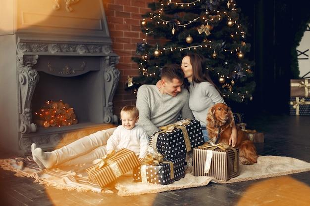 Famiglia con simpatico cane a casa vicino all'albero di natale Foto Gratuite