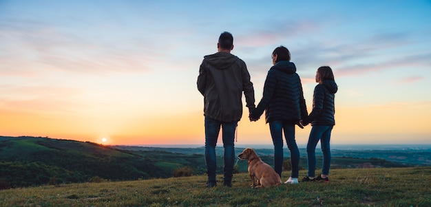Family with dog embracing while standing on the hill Premium Photo