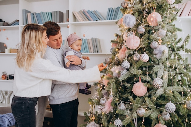Family with little daughter hanging toys on christmas tree Free Photo