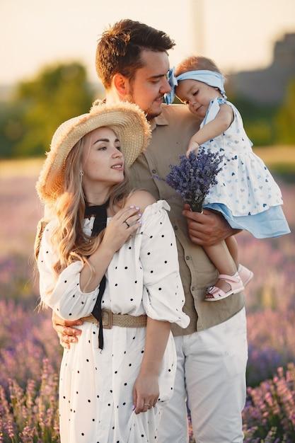 Famiglia con piccola figlia sul campo di lavanda. bella donna e bambino sveglio che giocano nel campo del prato. vacanze in famiglia in una giornata estiva. Foto Gratuite