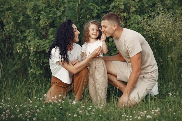 Семья с маленькой дочерью, проводящей время вместе в солнечном поле Бесплатные Фотографии