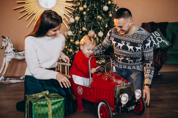 Family with little daughter with christmas gift by christmas tree Free Photo
