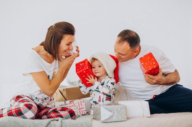 작은 아들과 크리스마스 선물 침대에 누워 가족 무료 사진