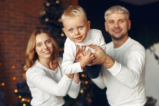 Семья с маленьким сыном дома возле елки Бесплатные Фотографии