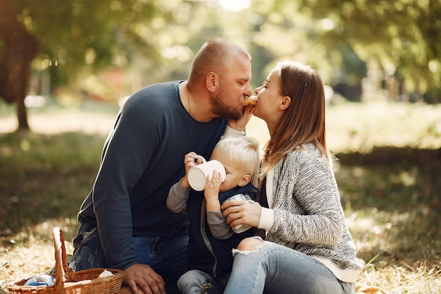Famiglia con figlio piccolo in un parco in autunno Foto Gratuite