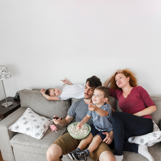 家庭でテレビを見ているポップコーンを持つ家族 Premium写真