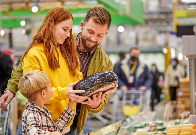 아들이 신선한 야채를 사서 가장 좋은 것을 선택하고, 여자가 남편과 구매를 논의하는 가족 프리미엄 사진