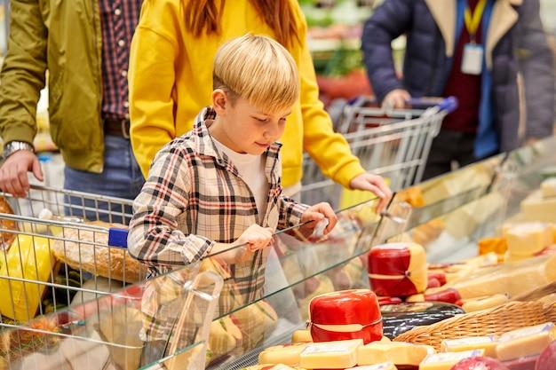 식품 매장에서 치즈를 선택하는 아들, 제품 쇼케이스를보고 논의하는 가족. 상점, 음식, 식료품 개념 프리미엄 사진