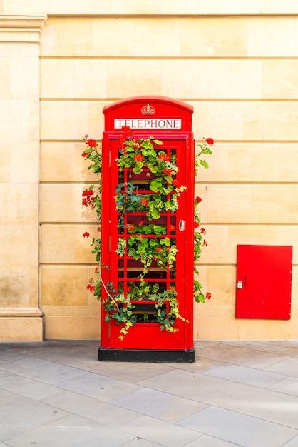 Знаменитая красная телефонная будка в лондоне с листьями Premium Фотографии
