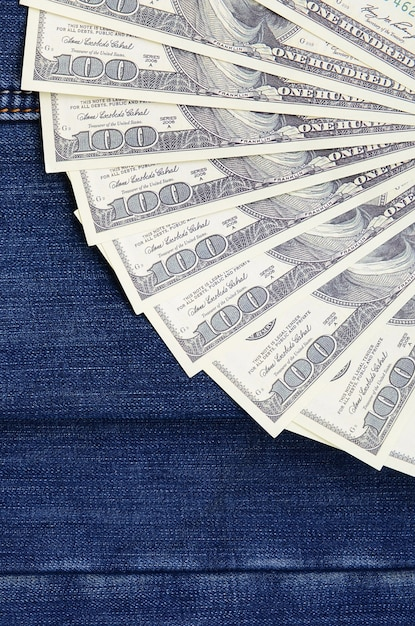The fan of a lot of us dollars is on a dark denim surface. background image Premium Photo