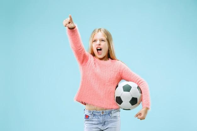 青い背景で隔離のサッカーボールを保持しているファンスポーツティーンプレーヤー 無料写真