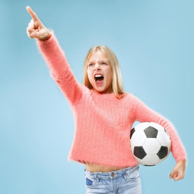 青いスペースで隔離のサッカーボールを保持しているファンスポーツティーンプレーヤー 無料写真
