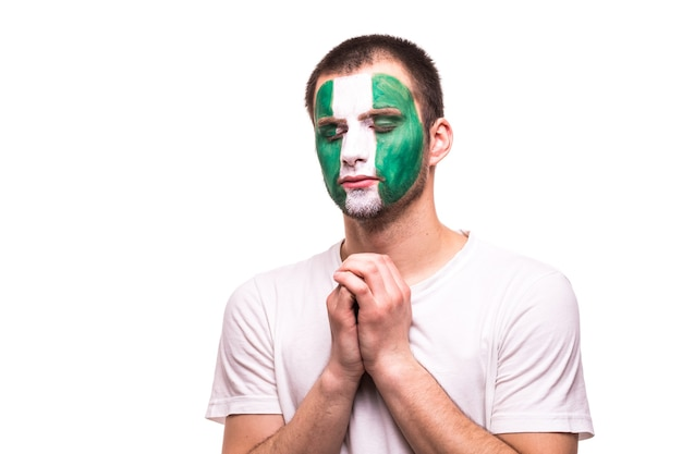 Болельщики сборной нигерии молятся с раскрашенным лицом на белом фоне Бесплатные Фотографии