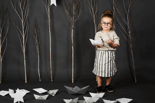 Fanny little girl with glasses on grey background with stars, trees and paper boats Premium Photo