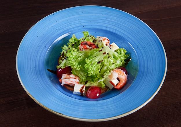 フェタチーズとブドウの素晴らしいおいしいエビのサラダを大きな青い素朴なプレートの上面図で提供しています 無料写真