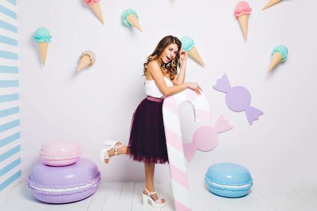 ピンクのキャンディーの杖を持って片足で笑顔で立っている濃い紫の緑豊かなスカートを着て幻想的な女の子。テーマの甘いパーティーを楽しんでいる陽気な女の子の全身像》。 無料写真