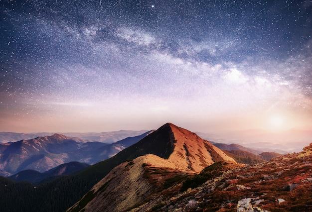 우크라이나의 산에서 환상적인 풍경입니다. 별과 성운과 은하계의 활기찬 밤하늘. 무료 사진