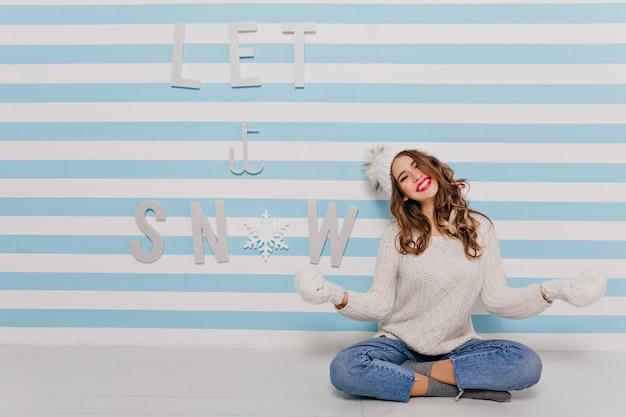 座って楽しんでいる幻想的ないたずらな白いモデル。若い女性が笑って「雪を降らせて」の碑文にポーズをとる 無料写真