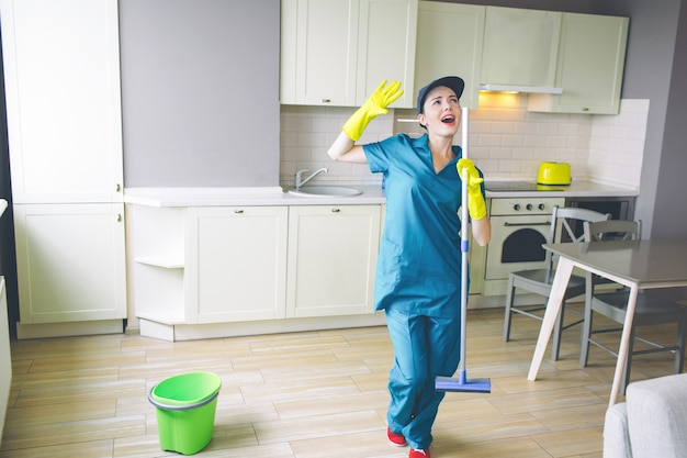 Fantastic woman stands in kitchen and holds mop in hands Premium Photo