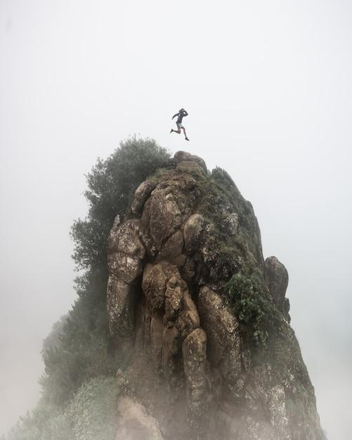 판타지 개념-흐린 안개 흰색 배경으로 높은 바위 절벽 위로 점프하는 사람 무료 사진