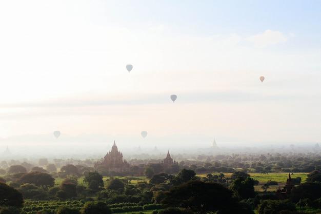 ファンタジーのコンセプト-お寺やお城の上を空の美しいフィールドの上を飛んでいる熱気球 無料写真